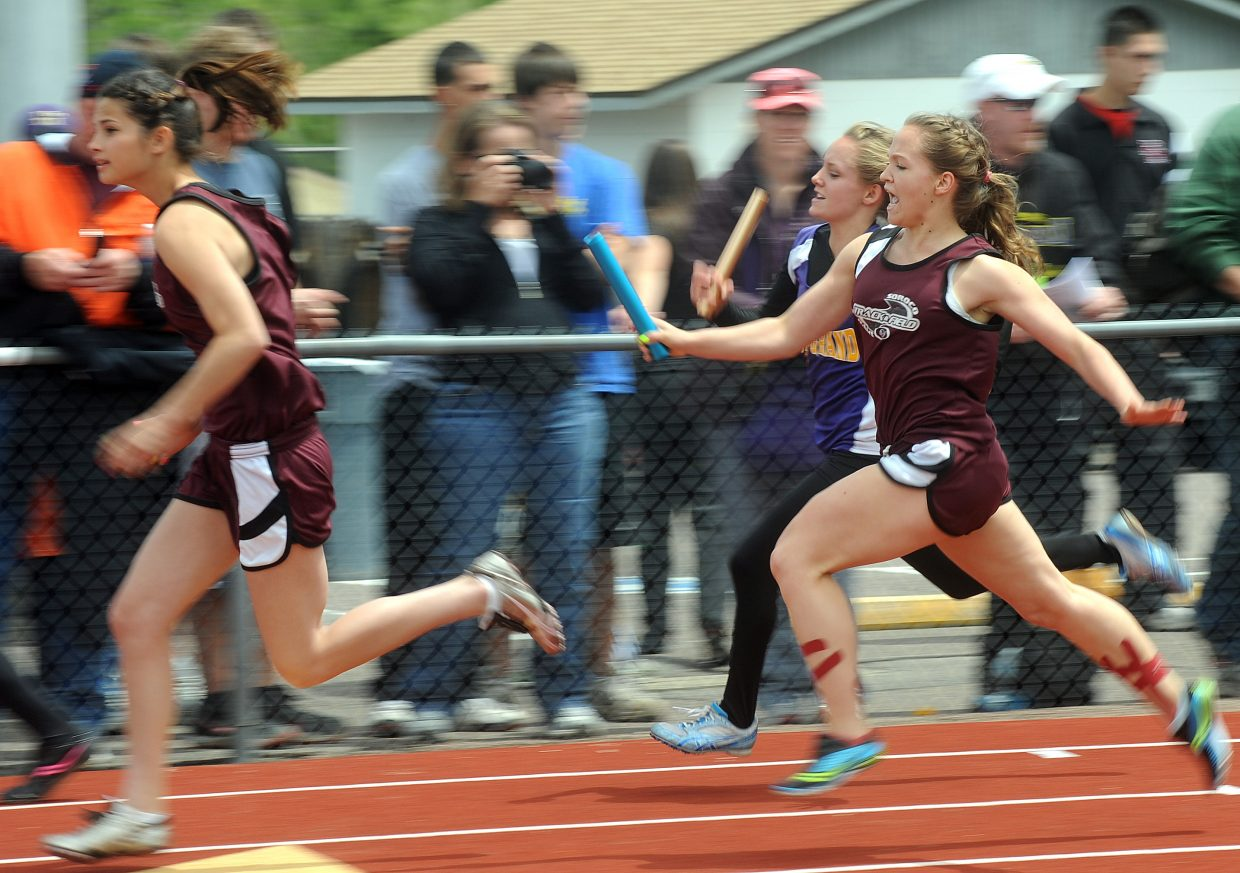 Lauryn Bruggink reaches to hand the baton to Ceanna Rossi in the 400-meter relay Friday at the state track meet in Lakewood.