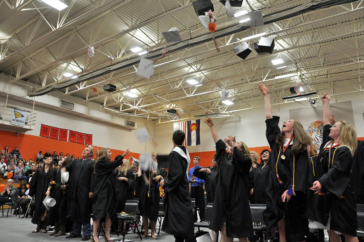 Hayden seniors throw their caps into the air Sunday after graduation.