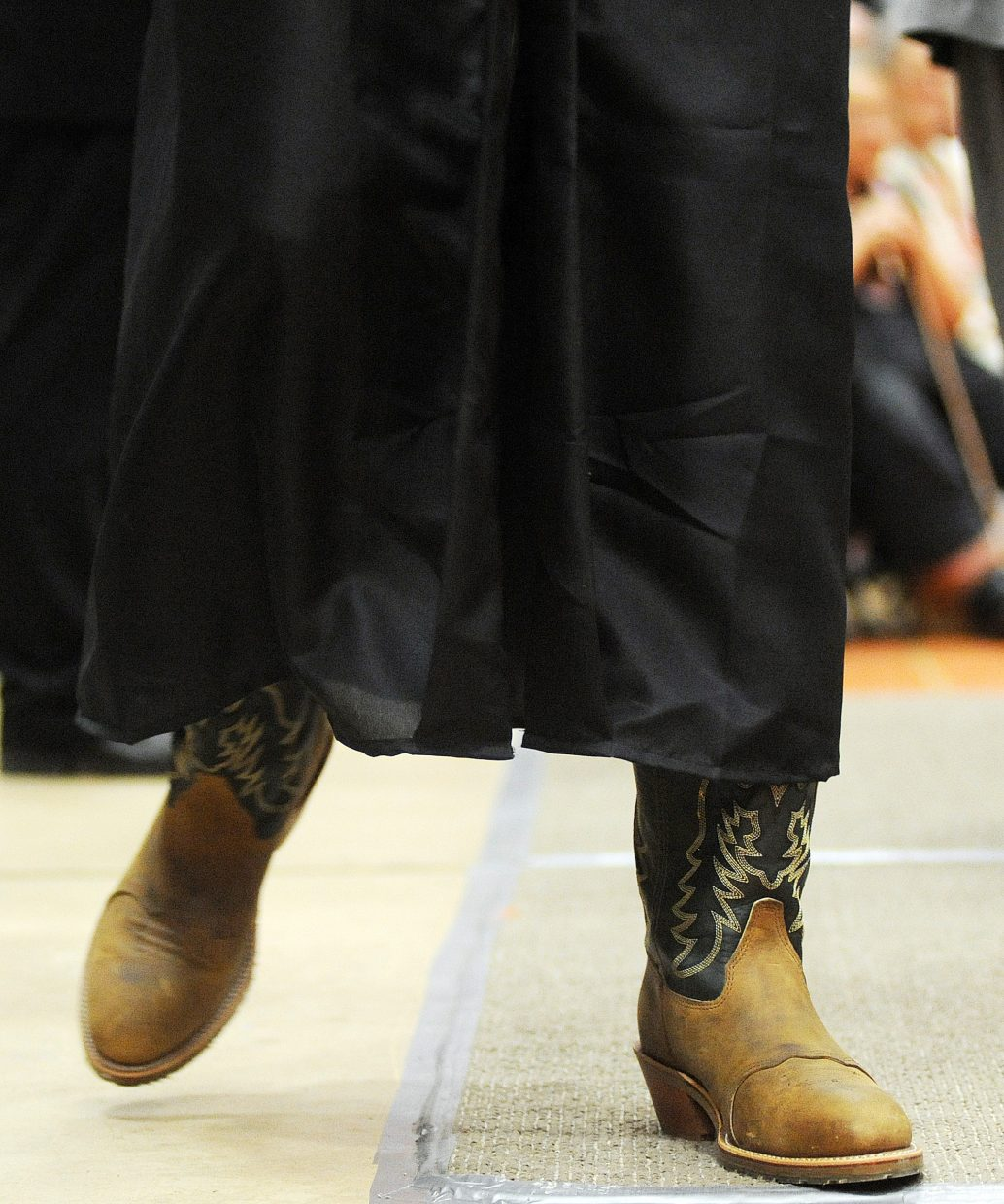Hayden High School senior Murphy Smartt walks away from the podium on Sunday at the Hayden graduation ceremony. The boots might come in handy for Smartt, who is headed to western Kansas to attend Fort Hays State University in Hays, Kan.