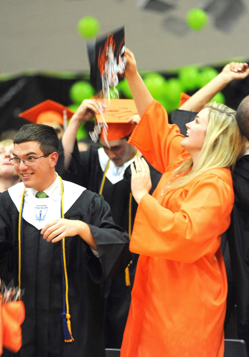 Mackenzi Frick throws her hat up in the air after Sunday's graduation ceremony at Hayden High School.