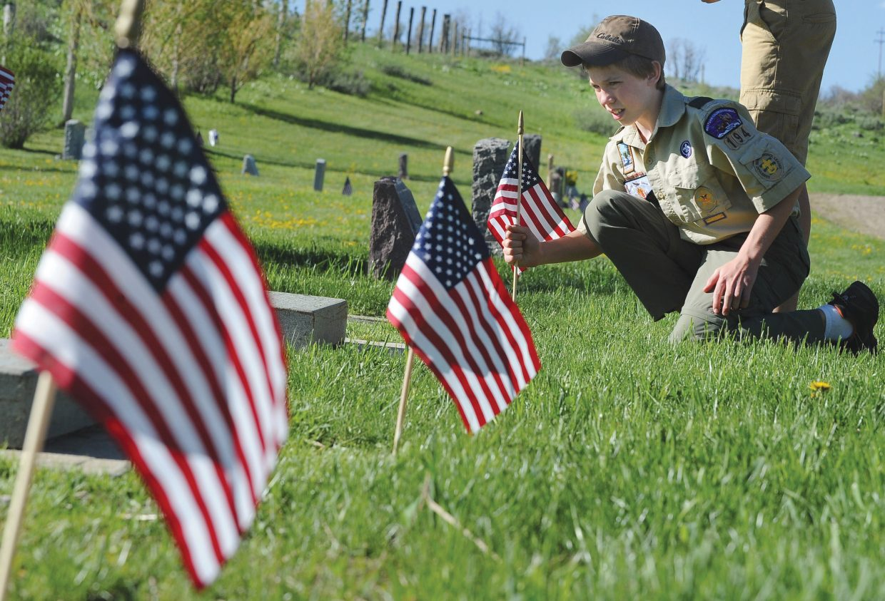 Boy Scout Kendall Hood places flags honoring Routt County veterans Thursday evening at Steamboat Springs Cemetery. The annual recognition of Memorial Day will take place at 11 a.m. Monday.