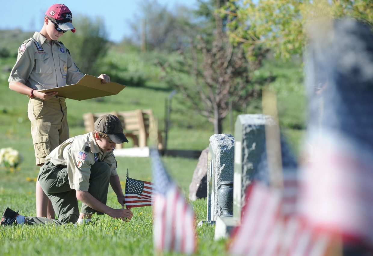 Boy Scouts Kendall Hood (kneeling) and Grant Pohlman place flags honoring Routt County veterans Thursday evening at Steamboat Springs Cemetery.