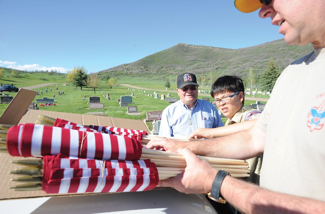 Veteran Jim Stanko, left, watches as Justin Peretz and his dad, John, gather flags to decorate the graves of Routt County veterans at Steamboat Springs Cemetery.