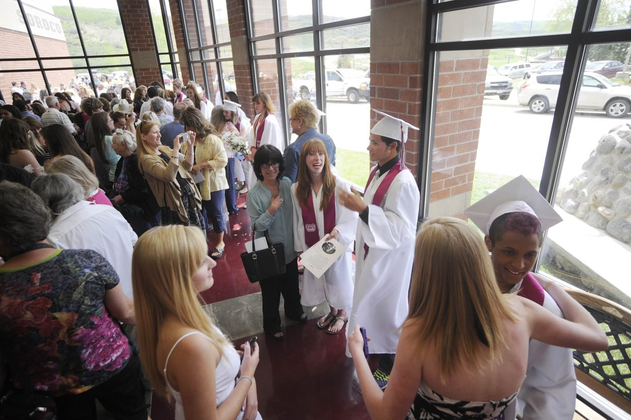 Soroco High School graduates visit with friends and family after Saturday's graduation ceremony.