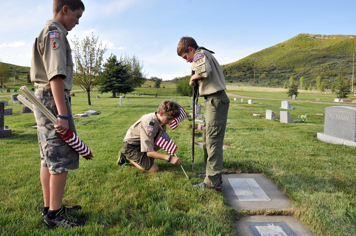 Boy Scouts, from left, Grant Pohlman, Zeke Kinnison and Kendall Hood place a flag in front of David Fogg's grave Thursday in the Steamboat Springs Cemetery. Fogg, a Soroco High School graduate, was killed in action in Vietnam when he was 18 years old.