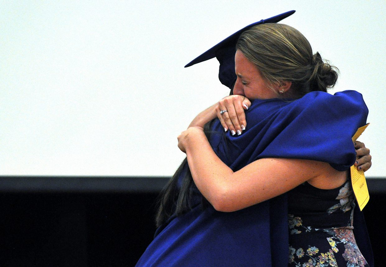 Heritage Christian School valedictorian Shealie Jenkins hugs her friend Hannah Mihaich on Sunday during the graduation ceremony.