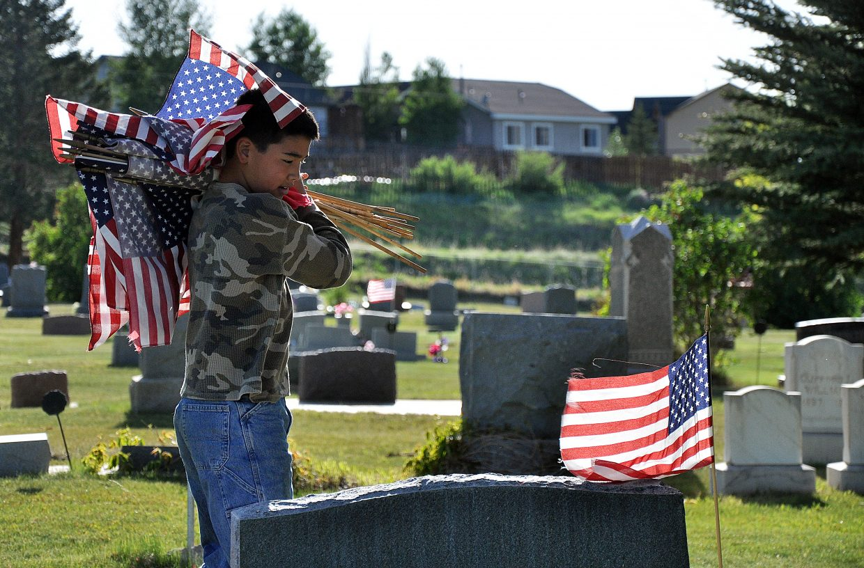 Hunter Hatcher picks up American flags Monday from graves in the Hayden Cemetery following the town's Memorial Day service.