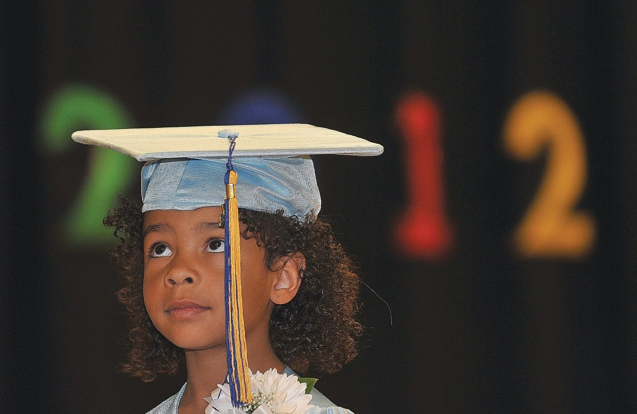 Heritage Christian School student Davina Grant listens while her teacher talks about her accomplishments this year. Davina was one of 10 graduates at the school's annual kindergarten graduation Wednesday morning.