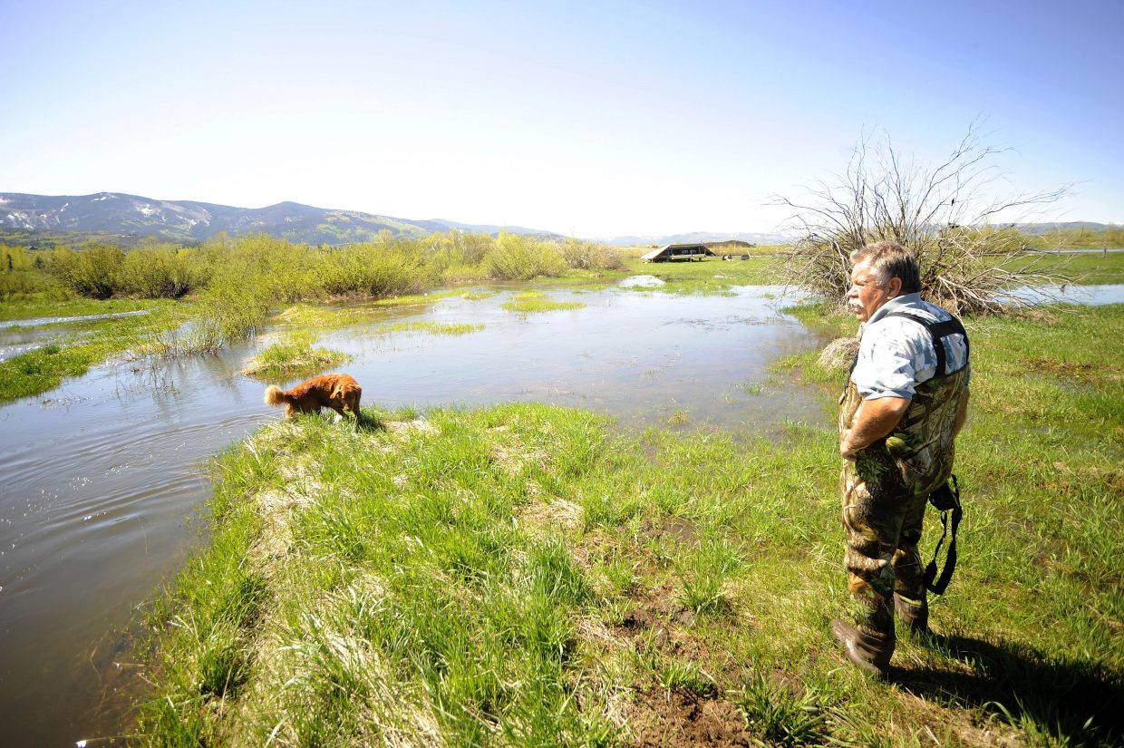 Curt Weiss surveys the flooding in southeastern Steamboat Springs on Tuesday morning.