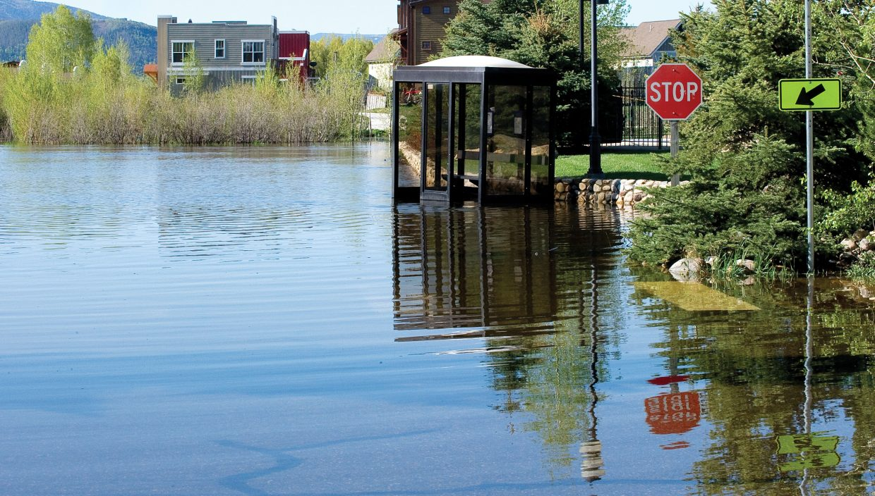 A bus shelter is swallowed by flood waters in a parking lot in front of the Steamboat Hotel on Tuesday morning. As temperatures continue to climb, more scenes like this one are expected.