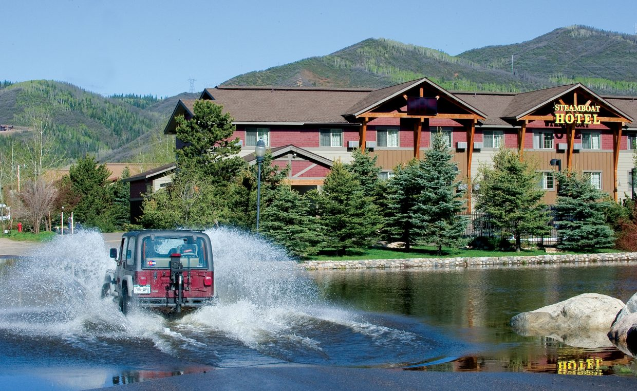 A Jeep drives through a flooded parking lot in front of the Steamboat Hotel on Tuesday morning.