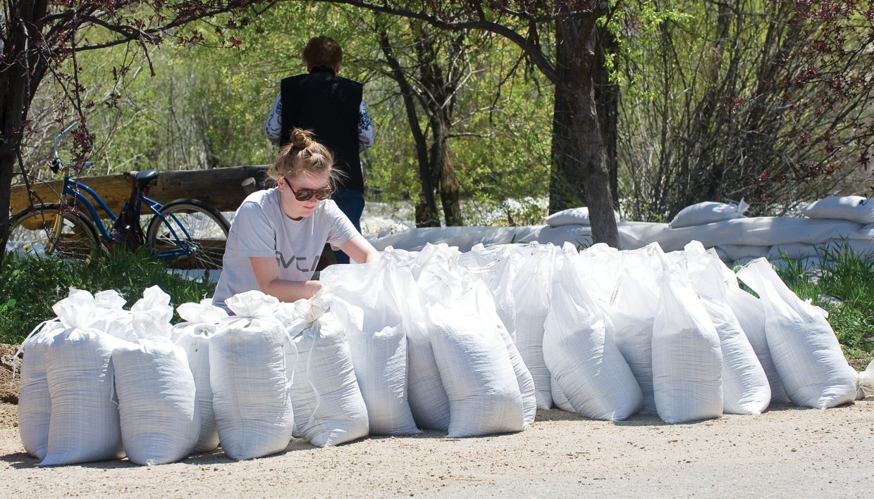 Kyla Yennie fills sandbags at Backdoor sports on Yampa Street Tuesday afternoon. The downtown business was preparing for higher waters on the Yampa River and possible flooding.