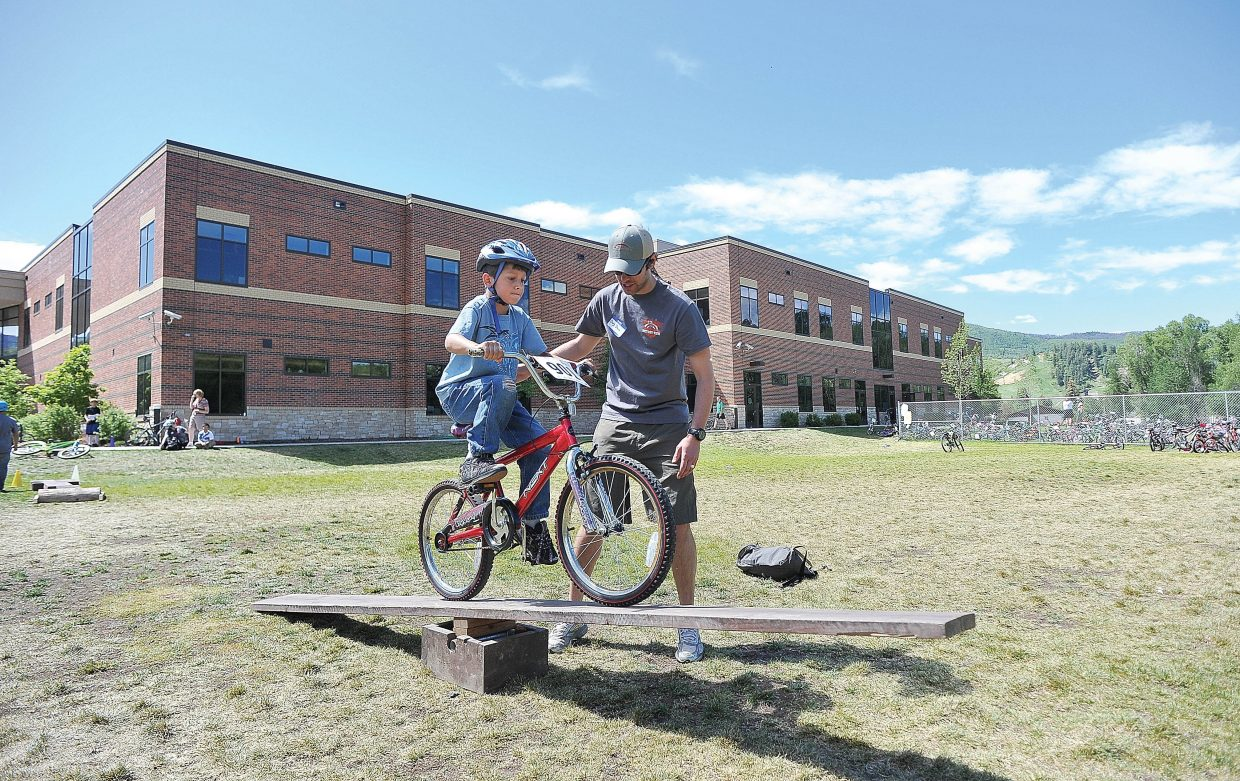 Volunteer Doug Davis helps third-grader Aiden MacGillivray over an obstacle during the Bike Rally at Soda Creek Elementary on Friday.