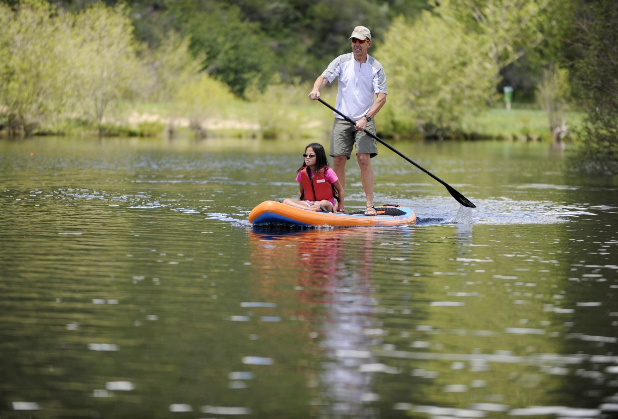 Steamboat Springs resident Mel Stewart and his daughter Emma stand-up paddleboard Saturday during the Yampa River Festival.