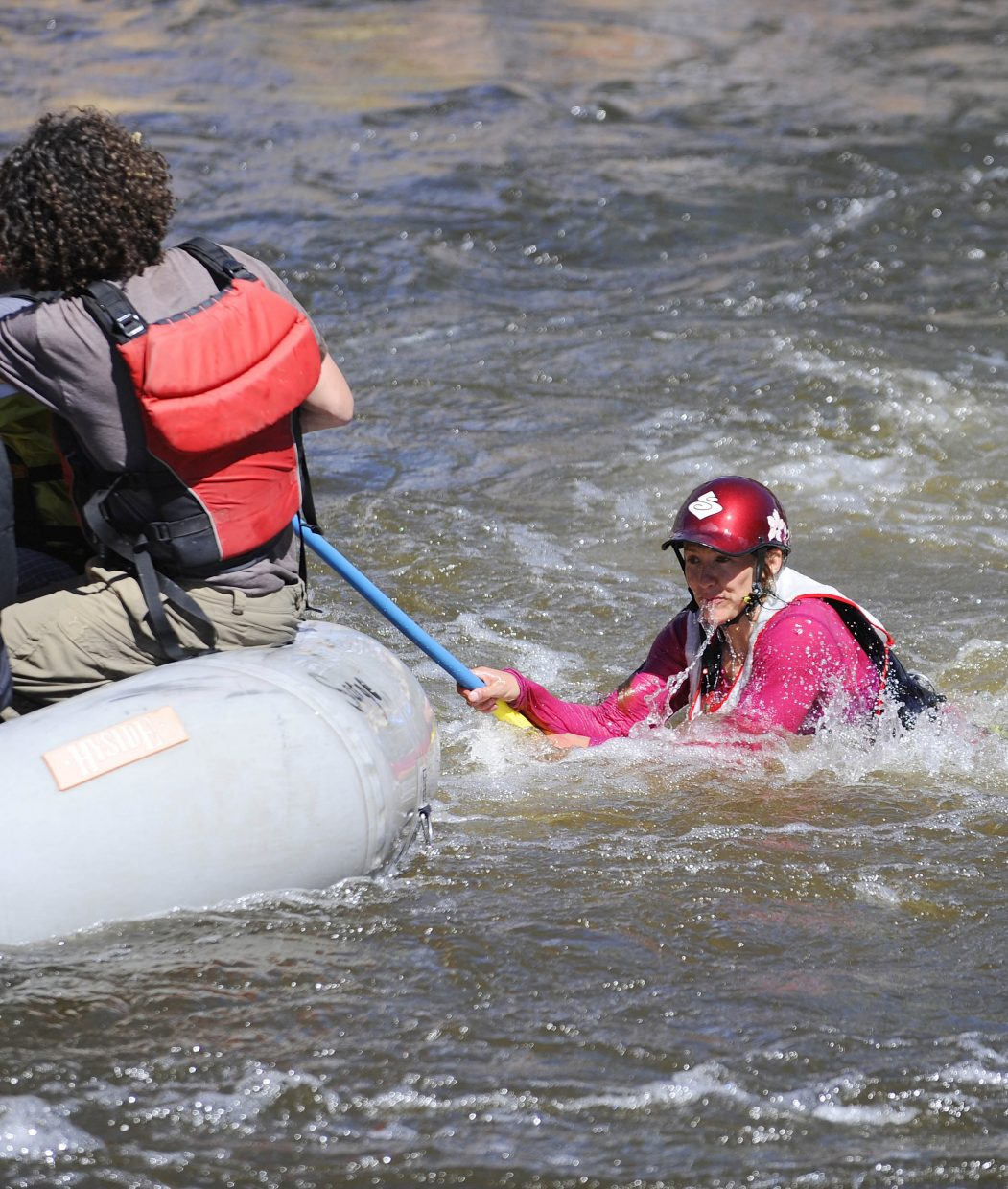 A rafter holds on to a paddle Saturday during the Yampa River Festival raft race.