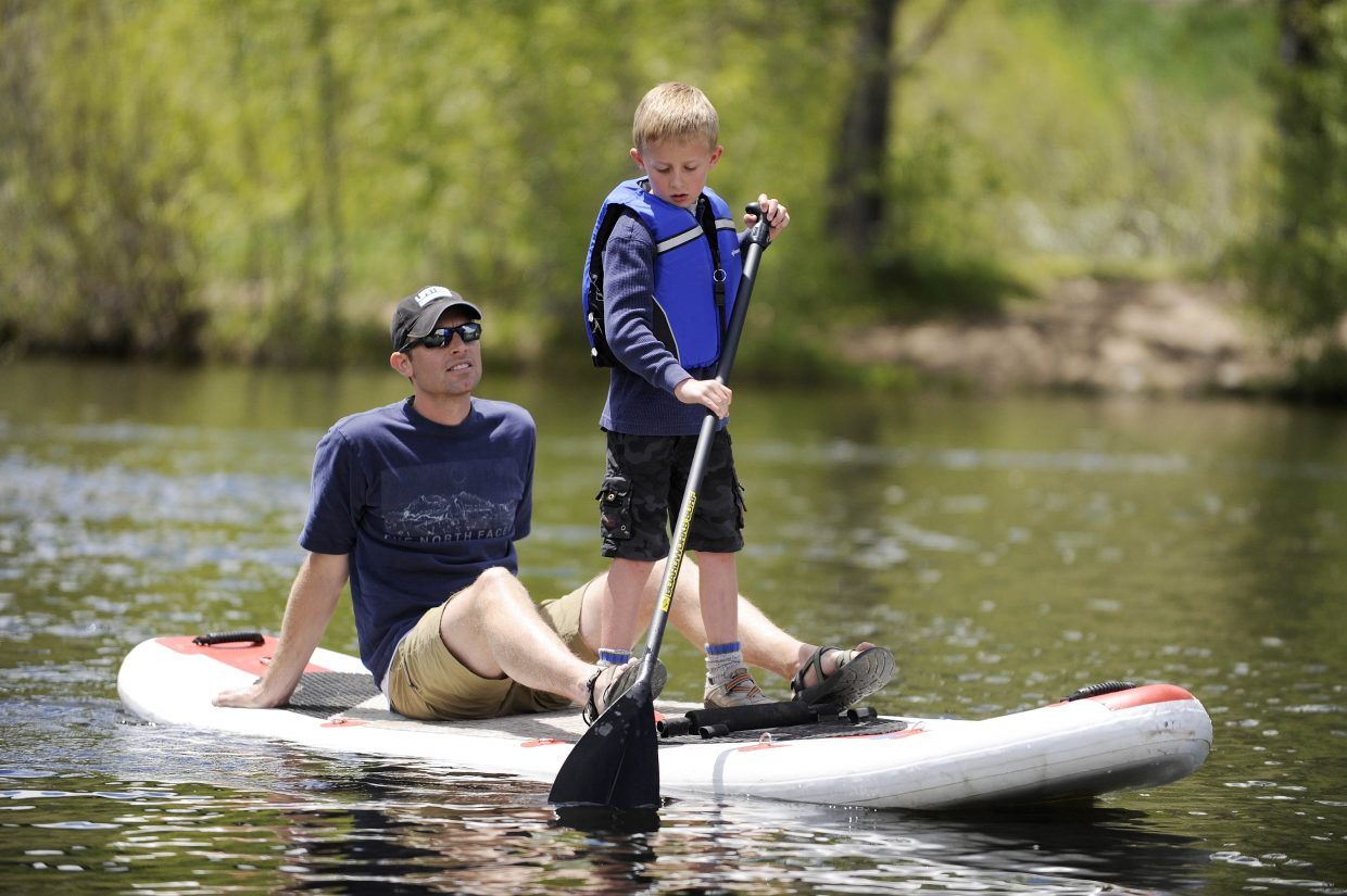 Highlands Ranch resident Ben Warta and his son Landon stand-up paddleboard Saturday during the Yampa River Festival.