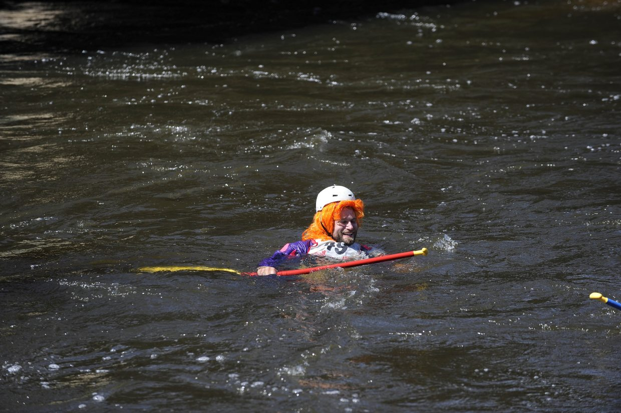 Kerry Lofy floats down the river after falling out of a raft Saturday during the Yampa River Festival raft race.