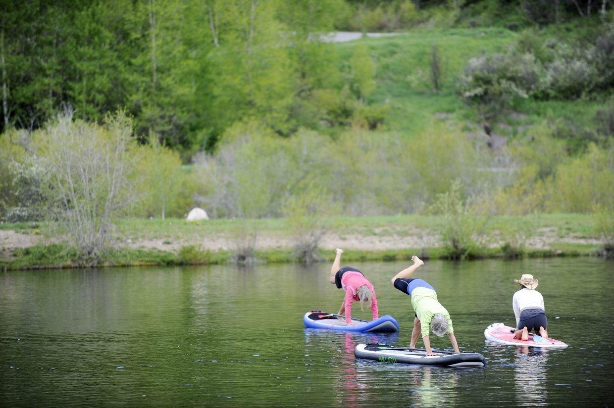 A group does stand-up paddleboard Yoga on Saturday during the Yampa River Festival.