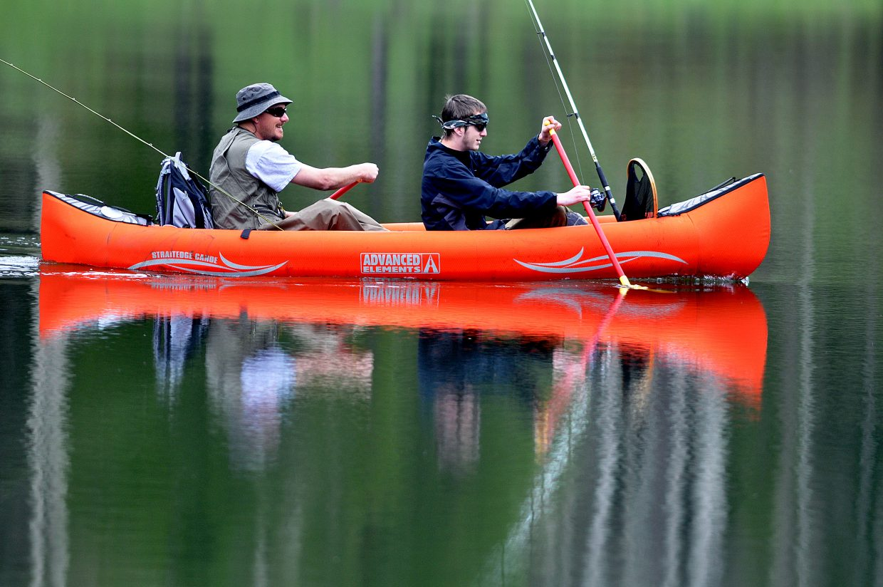 Jason Hirsch, left, and his son, Austin, fish from a canoe on Saturday in the calm waters of Pearl Lake in North Routt County.