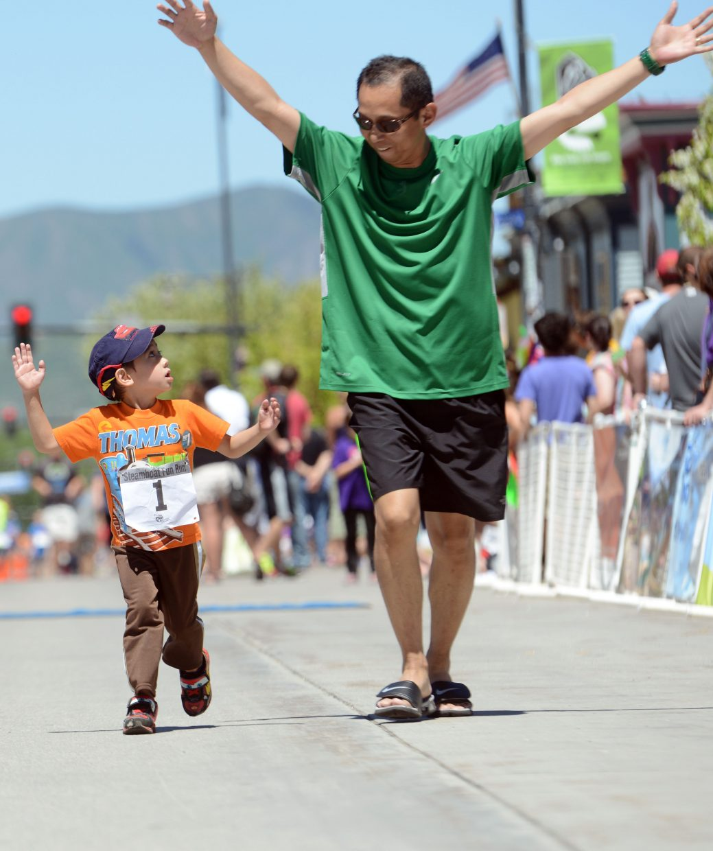 Ritchie Hernandez gives his son, Nevaeh, 5, a tip on the correct way to cross the finish line during the children's Fun Run at the Steamboat Marathon. Hernandez had the scoop thanks to his finishing the half-marathon earlier in the day.