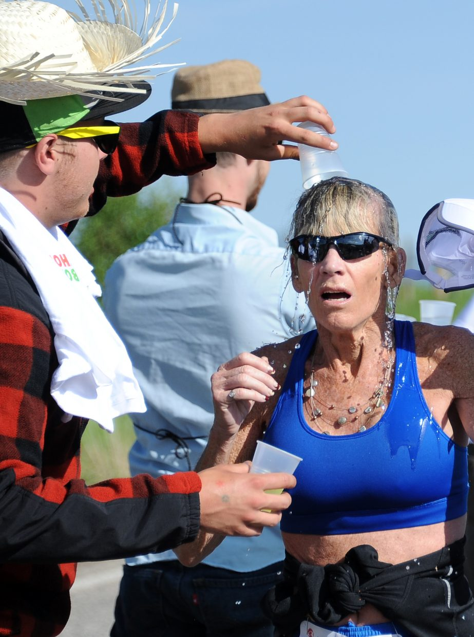 Steamboat Springs' Barbara Jones asks to be doused with water at the Rex's family of restaurants Hawaiian-themed aid station Sunday during the annual Steamboat Marathon. She ran the half marathon, finishing in 2 hours, 10 minutes and 42 seconds.