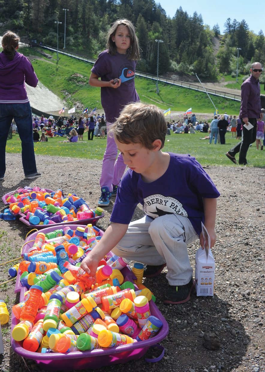 Xander Delke picks up a bottle of bubbles before Monday afternoon's memorial service for Asher Lesyshen-Kirlan at the base of Howelsen Hill. The hundreds of people who came out blew bubbles at the end of the service as a tribute to Asher.
