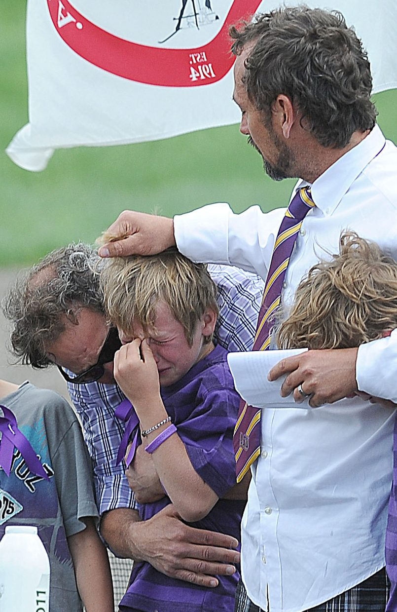 """Mike Kirlan hugs Oliver Cardillo during Monday afternoon's memorial service for Kirlan's son, Asher Lesyshen-Kirlan at the base of Howelsen Hill. The boys came on stage to sing the """"Star Spangled Banner"""" as part of a tribute to the 9-year-old boy who died last week. Oliver's father, John Cardillo, middle, and his brother, Henry, also were on stage for the tribute."""