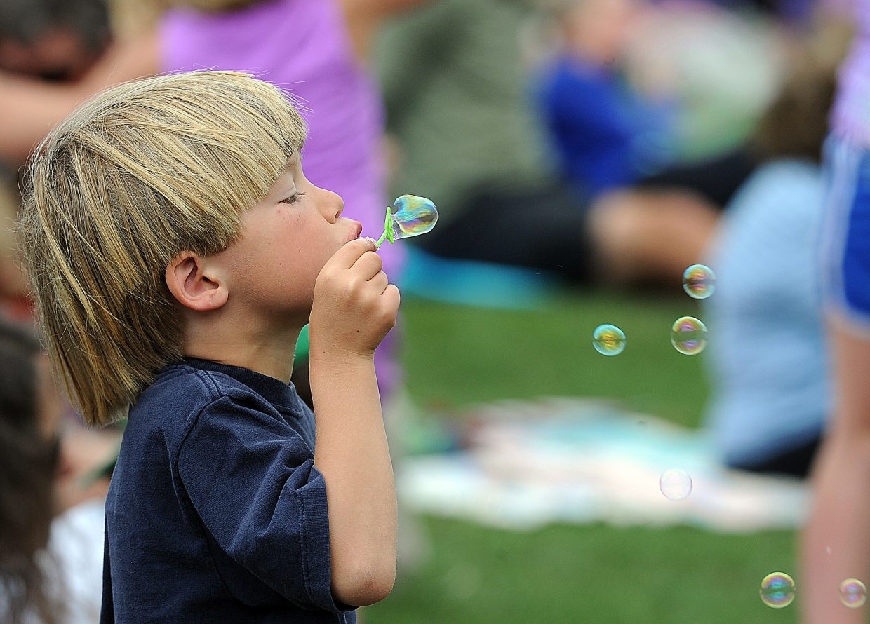 A young child blows bubbles during a memorial service for 9-year-old Asher Lesyshen-Kirlan on Monday afternoon at the base of the ski jumps at the Howelsen Hill Ski Area, where Asher spent many winter days.