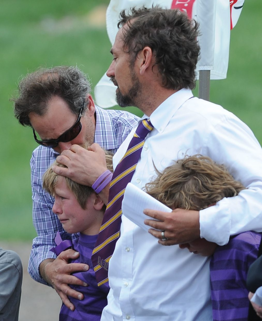 """Mike Kirlan hugs Oliver Cardillo during Monday afternoon's memorial service for Kirlan's son, Asher Lesyshen-Kirlan, at the base of the Howelsen Hill jump complex. The boys came on stage to sing the """"Star Spangled Banner"""" as part of a tribute to the 9-year-old boy, who died last week. Oliver's father, John Cardillo, middle, and his brother, Henry, also were on stage for the tribute."""