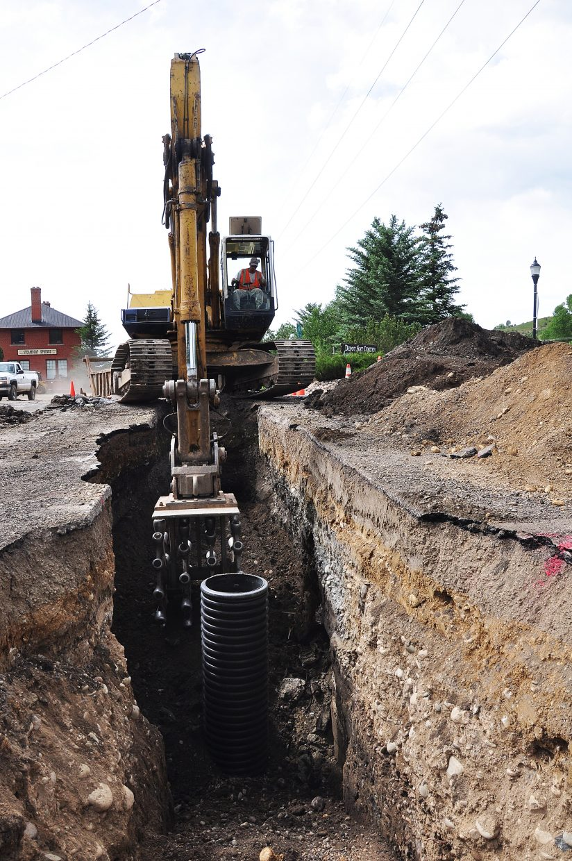Scott Scherer and crews from Native Excavating work Monday to replace a water main near Bud Werner Memorial Library. City engineer Danny Paul said the $1.6 million project will replace 6,000 linear feet of old water main.