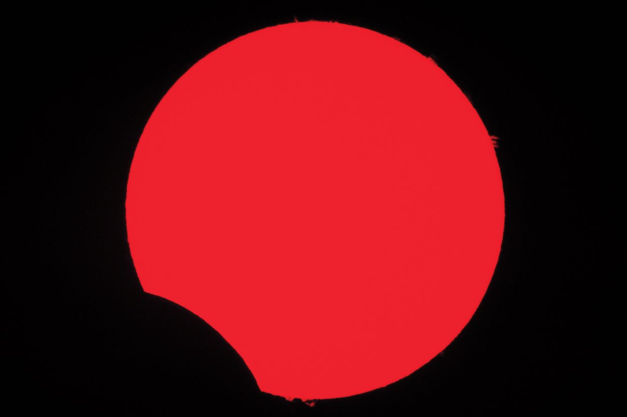 Earth-sized solar prominences flare up around the edge of the sun as the moon glides between the Earth and the sun on May 20. This is the view through a hydrogen-alpha solar telescope, which allows solar details to be seen that are otherwise hidden from view.