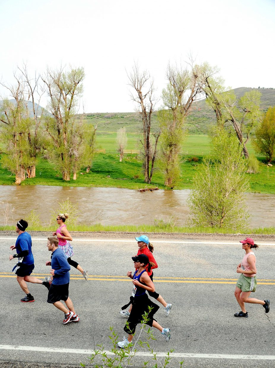 A pack of runners work their way toward Steamboat Springs on Sunday in the Steamboat Marathon.