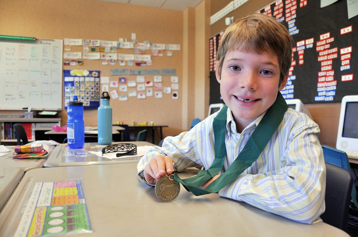 Shane Lambert, 8, shows off the medal he earned by shining on the ACT Explore test designed for students who are about to enter high school. The Soda Creek Elementary School student's performance on the math section of the test placed him in the top 10 percent of third-graders in seven states.