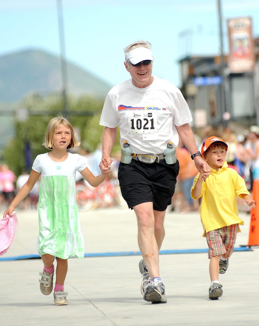 Tom Hurt jogs toward the finish line hand-in-hand with his grandchildren, 6-year-old Cadance and 4-year-old Baylor, Sunday while finishing up the half-marathon race during the Steamboat Marathon.