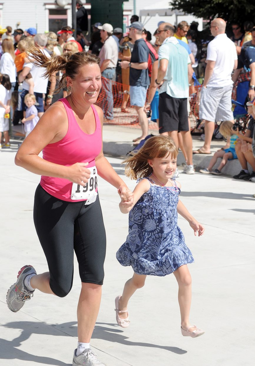 Denver half marathon runner Rebecca Wiggins runs with 5-year-old daughter Kate Tinsley on Sunday during the Steamboat Marathon.