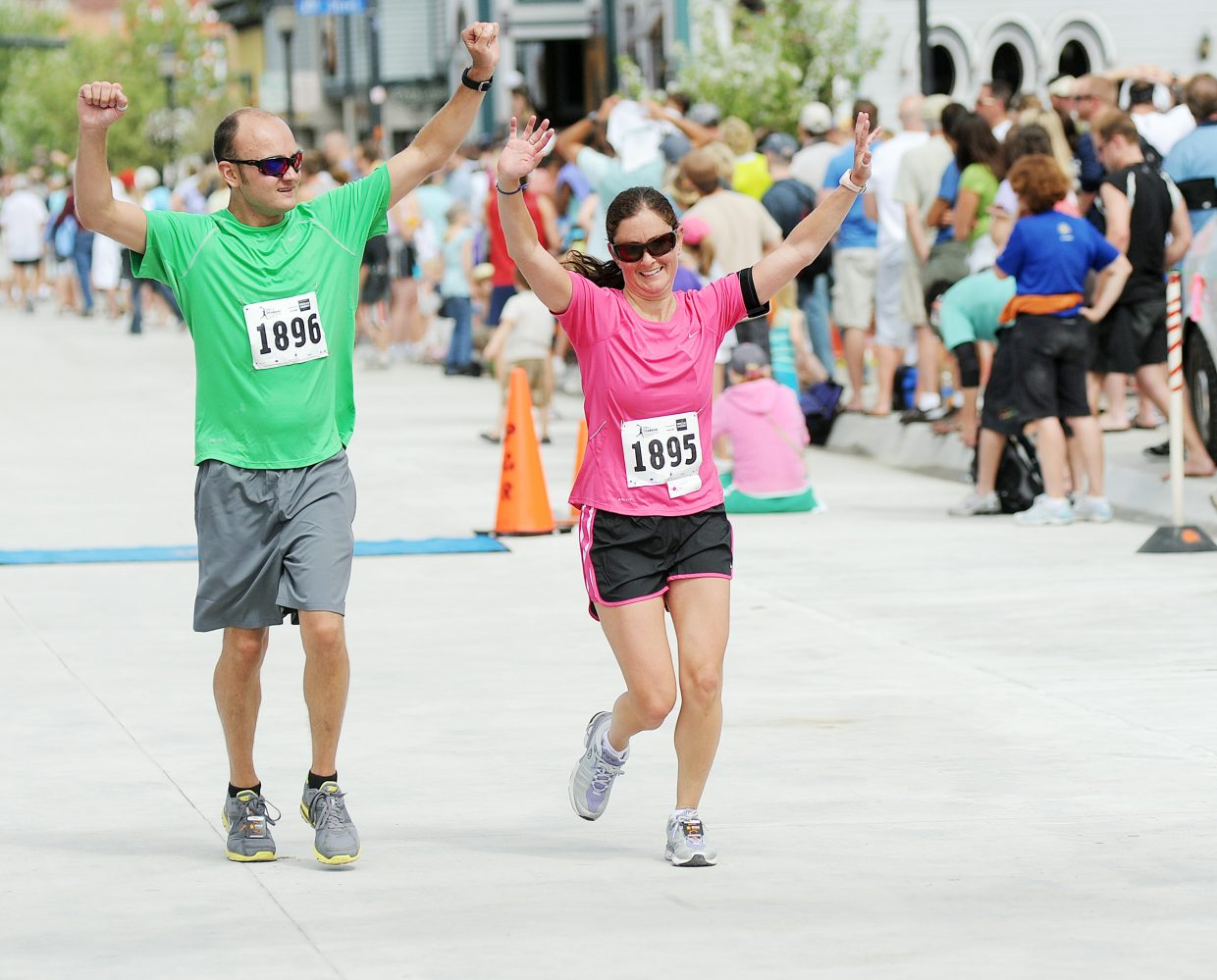 Brandon Doza and Michelle Quittner, both of Breckenridge, soak in their finish line moment during the half marathon Sunday at the Steamboat Marathon.