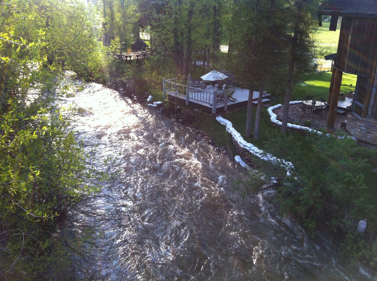 Soda Creek nears the top of its banks as it flows behind a home in downtown Steamboat Springs on Monday morning.
