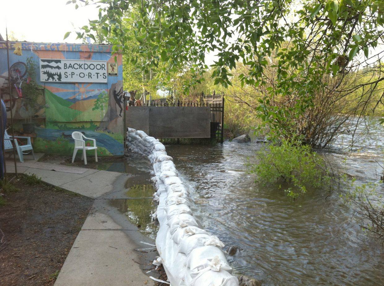 A wall of sandbags helps keep the Yampa River out of Backdoor Sports in downtown Steamboat Springs on Monday.