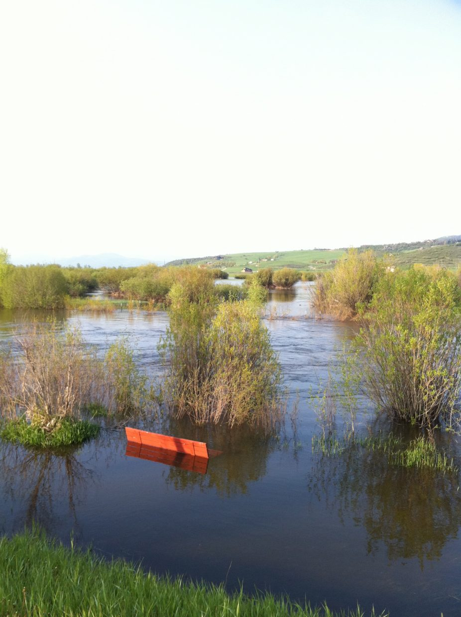 A bench is submerged by Yampa River floodwaters at Rotary Park in Steamboat Springs on Monday morning.