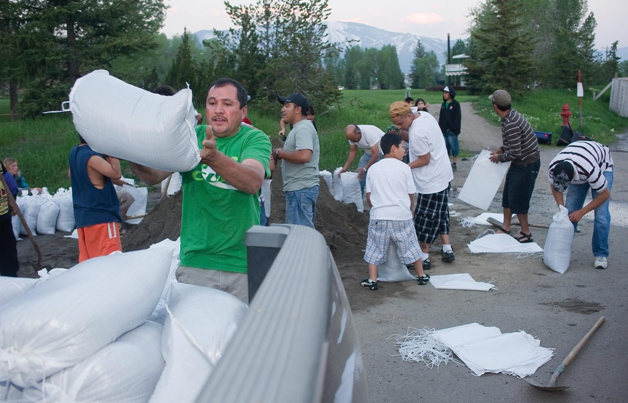 Dream Island resident Jorge Torres throws a sandbag into the back of his pickup truck Monday evening as he prepared for a long night in the mobile home park on the edge of downtown Steamboat Springs. Many residents in the park spent the evening filling and stacking sand bags in front of their homes as the waters of the Yampa River began to spill into the area.