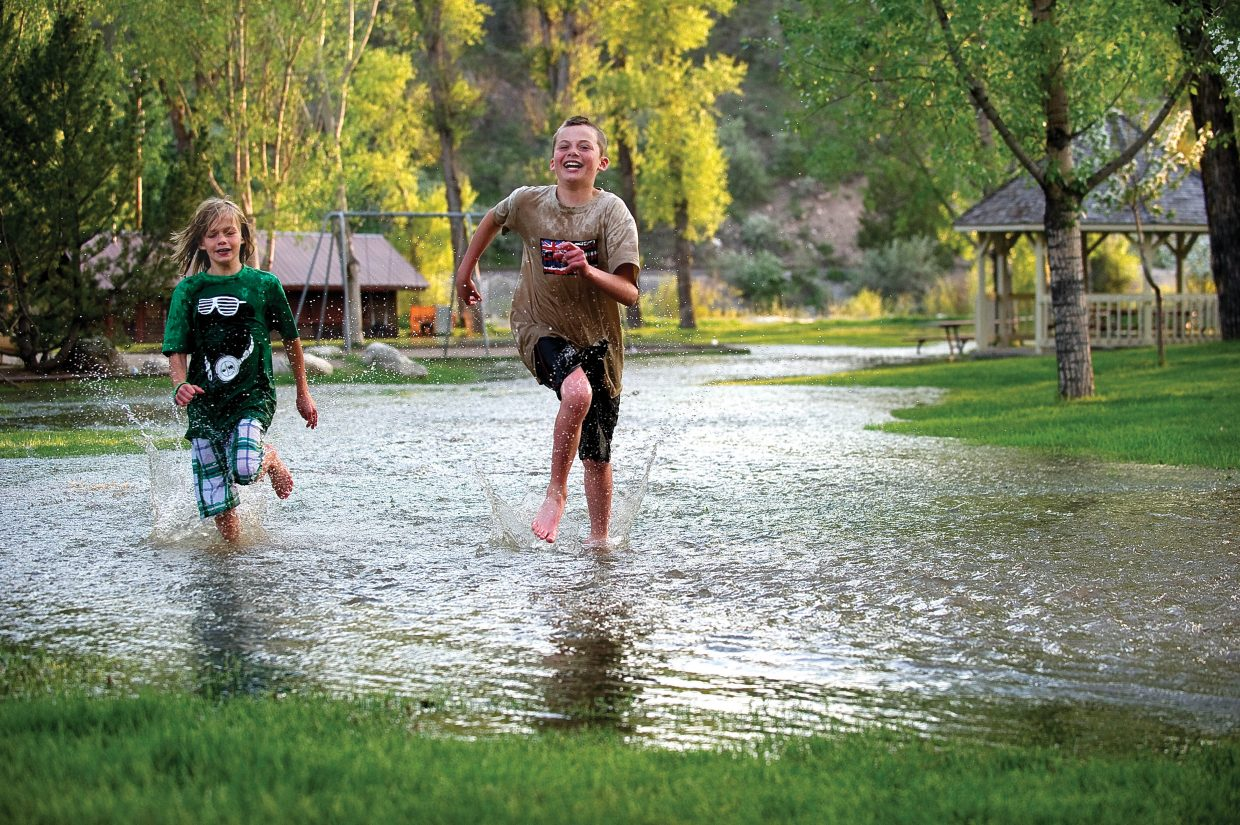 Cole Spradlin, front, and his brother Tifton run through the water in Little Toots Park on Monday evening in downtown Steamboat Springs. The high waters of Soda Creek spilled over a retaining wall forming a shallow river of water that flowed from one end of the park to the other.