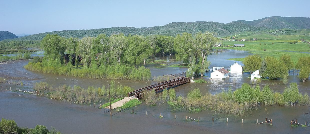 The high water of the Elk River threatens a home off Routt County Road 42. The home's driveway and several buildings also have been swallowed by the Elk's fast-moving water.