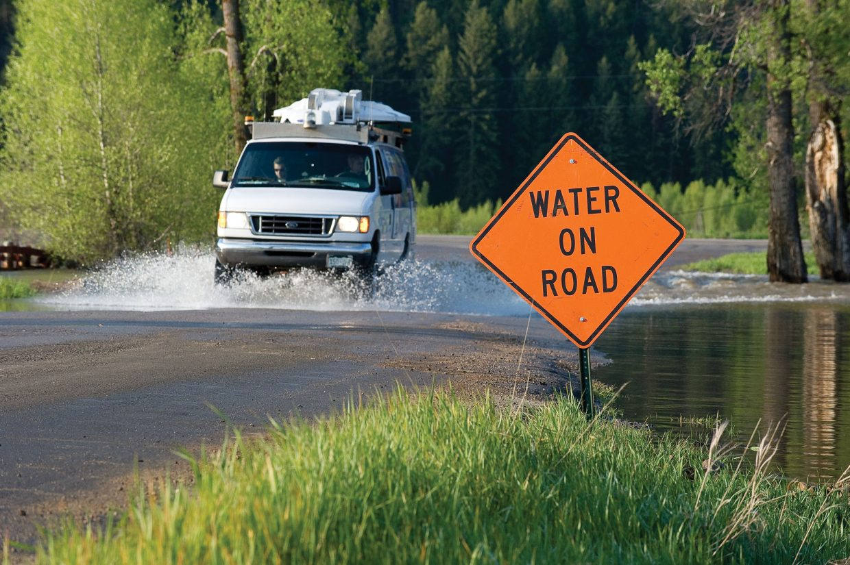 A news van from Channel 4 in Denver drives through water on Routt County Road 44 on Monday while covering flooding in the Yampa Valley.