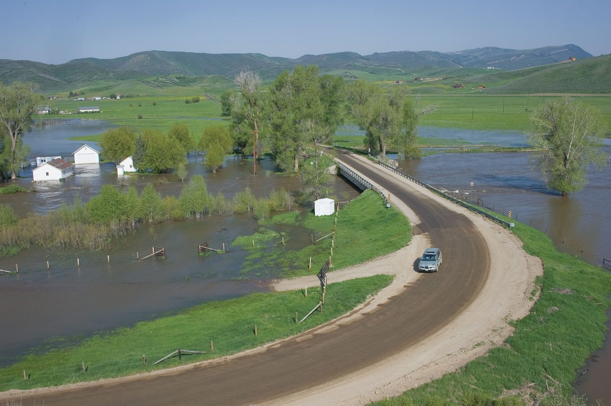 A car drives along Routt County Road 42 on Monday morning where the Elk River has overflowed its banks just west of Steamboat Springs.