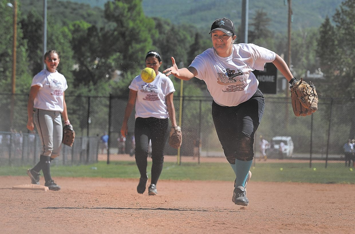 Shelby Martinez tosses a ball to a coach during a drill Wednesday afternoon at a girls softball camp. The first of six youth Triple Crown tournaments begins Friday.