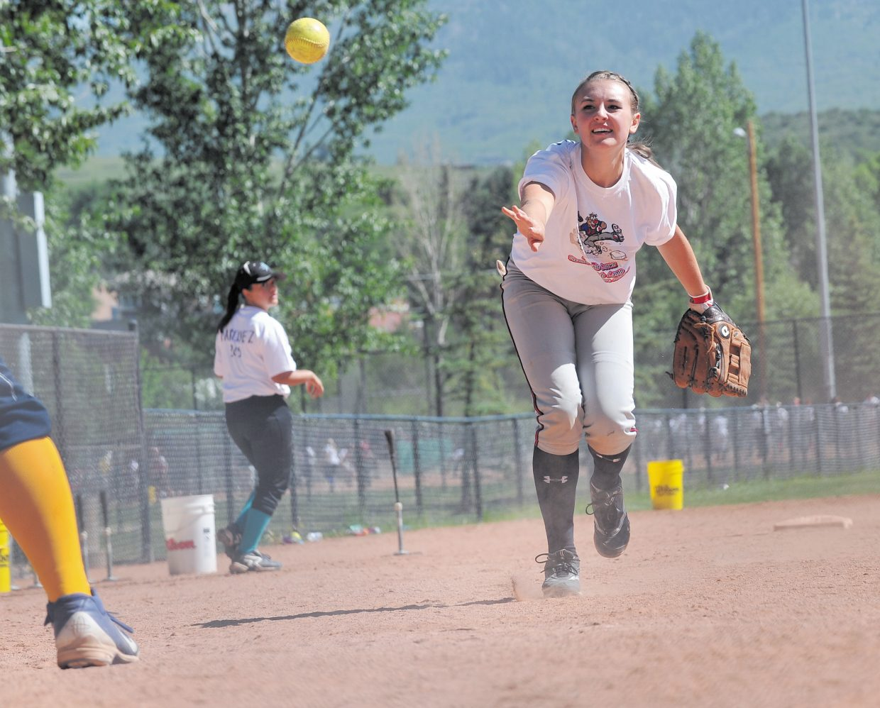 Morgan Zanski tosses a ball to a coach during a drill Wednesday afternoon at a girls softball camp hosted by Triple Crown.