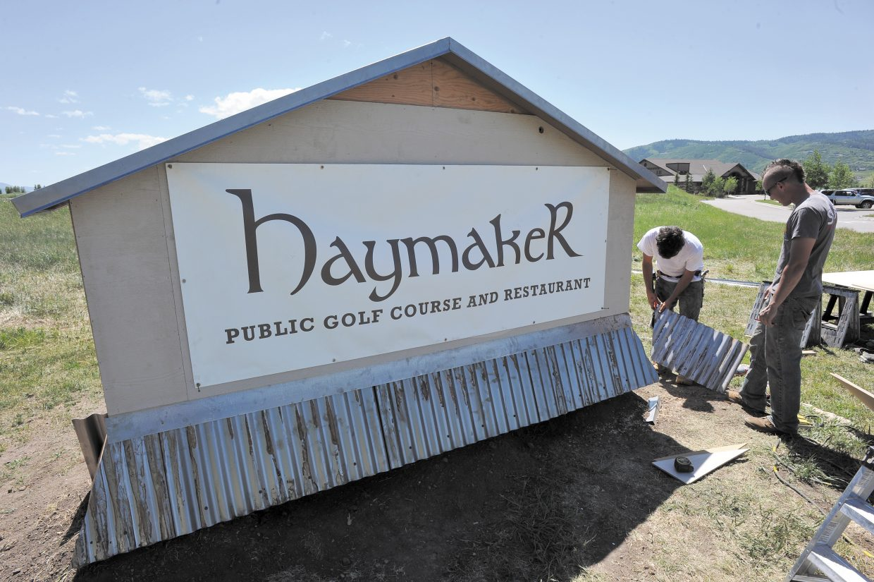Kyle Buckler, left, and Lucas Sullivan, of Calcon Constructors, work on a new sign in front of the Haymaker Golf Course on Wednesday afternoon. The city's 1 percent lodging tax will be freed up from supporting the golf course in 2014, and the city on Wednesday initiated the first step in identifying the future use of the tax.