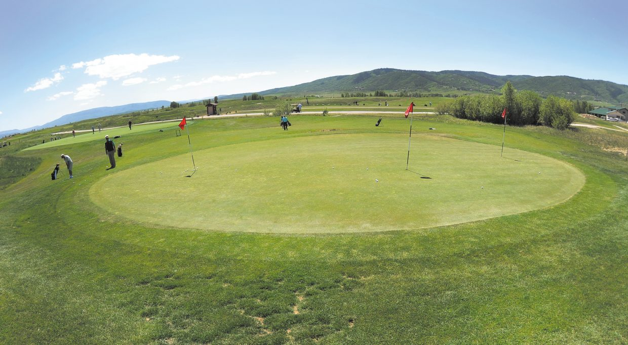Golfers use the practice facilities at the Haymaker golf course Wednesday afternoon. The city's 1 percent lodging tax will be freed up from supporting the golf course in 2014 , and the city on Wednesday initiated the first step in identifying the future use of the tax.