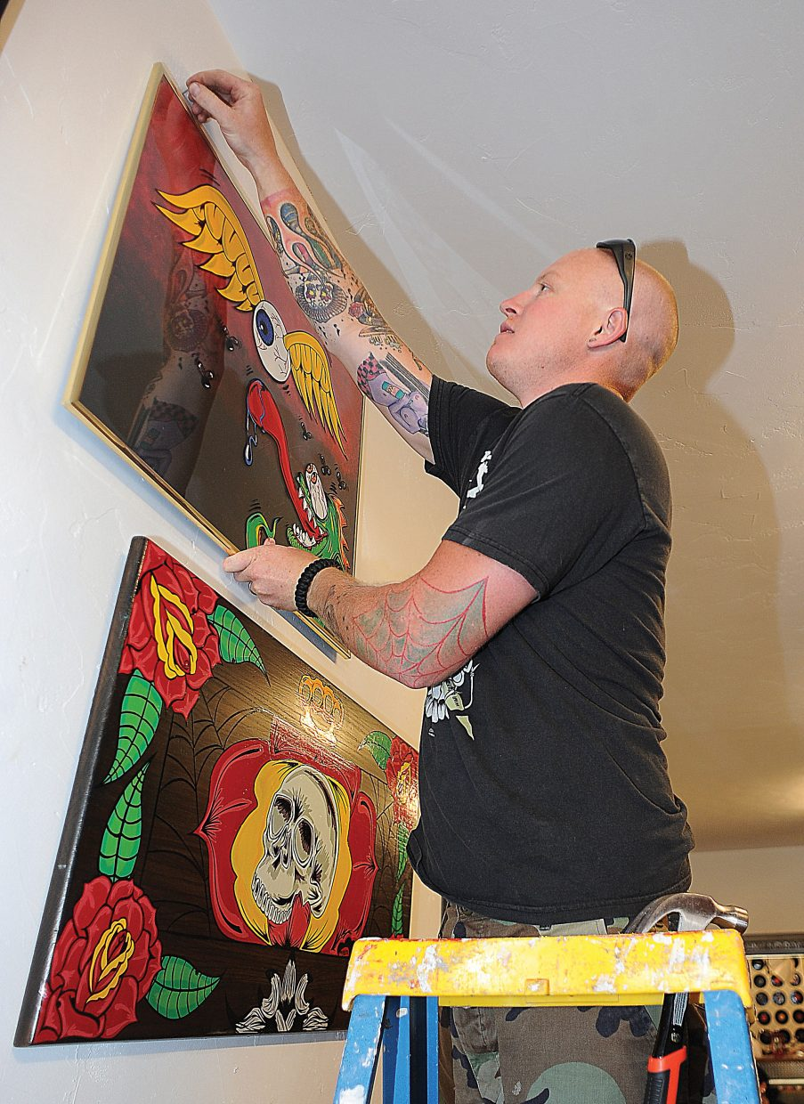 Local artist Mike Moore holds up one of his creations while hanging his art at Deluxe Tattoo in downtown Steamboat Springs on Thursday afternoon. Moore's work will be featured this month at the tattoo shop.