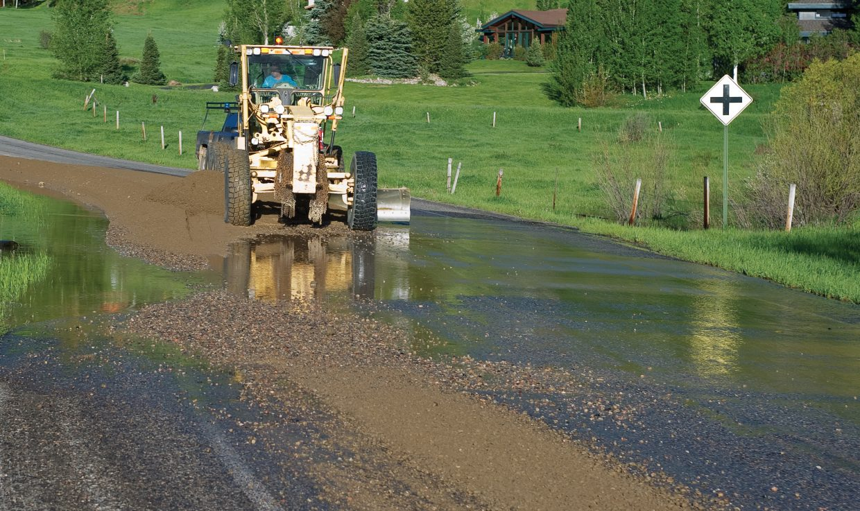 Routt County Road and Bridge crews use sand to stop water from the Yampa River from running across Mount Werner Road near Tree Haus neighborhood in Steamboat Springs on Tuesday morning.